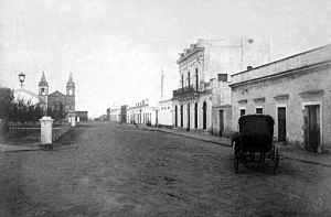 "Nogoyá - View of the city in 1887. At left background, the ""Basílica Nuestra Señora del Carmen""."