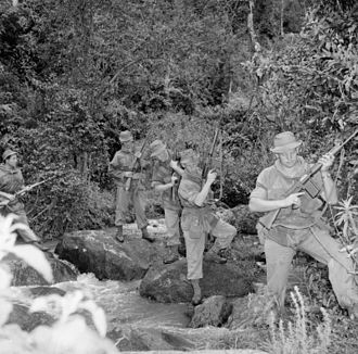 Mau Mau Uprising - British Army patrol crossing a stream carrying FN FAL rifle (1st and 2nd soldiers from right); Sten Mk5 (3rd soldier); and the Lee–Enfield No. 5 (4th and 5th soldiers)