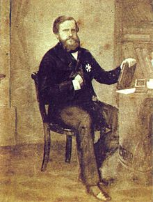 Photograph of a man with a full beard and dressed in a dark frock coat who is seated at a table holding a book with bookshelves in the background