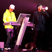 A colour photograph of the two members of the Pet Shop Boys on a stage with a synthesizer and a microphone respectively