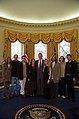 President Bill Clinton poses for a photo with musician Sheryl Crow and her band in the Oval Office.jpg