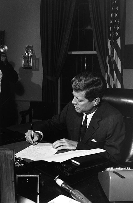President Kennedy signs the Proclamation for Interdiction of the Delivery of Offensive Weapons to Cuba at the Oval Office on October 23, 1962. President Kennedy signs Cuba quarantine proclamation, 23 October 1962.jpg