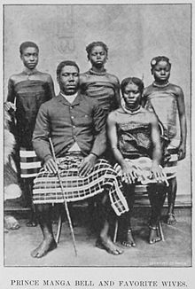 Black and white photograph of Prince Manga Bell of Cameroon with four of his favourite wives.