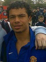 A photograph of a mixed-race man with short, curly, black hair wearing a blue shirt.