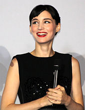 A smiling woman with short hair wears a black dress.lol