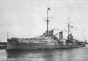 A large gray warship sits in harbor, wispy smoke billows lazily from two smoke stacks
