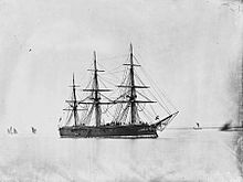 A large black warship with three tall masts