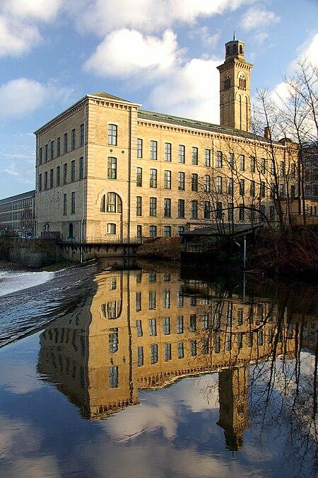 مصنع مبني من الحجارة تظهر خلفه السماء زرقاء فاقعة، كما ويظهر انعكاس هذه الصورة بكاملها في المياه.