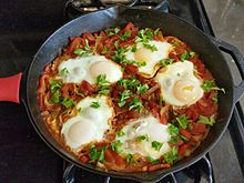Shakshouka with five cooked eggs on top of tomato sauce in cast iron skillet