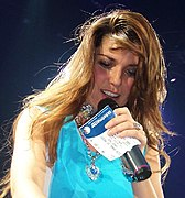 Photographie de Shania Twain en train de chanter, un ticket en main.