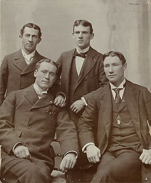 John McGraw - A young McGraw (standing, to the right), 22 years old, with outfielder Joe Kelley (seated left), shortstop Hugh Jennings (seated right), and Willie Keeler (standing left)