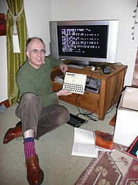 Steve Vickers sitting next to a flatscreen television which is connected to a Jupiter ACE.