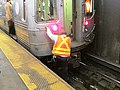 Subway motorman climbs out of D train.jpg