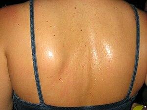 The sweaty back of a statuesque blonde attendi...