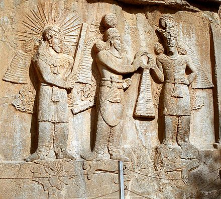 Investiture of Sassanid emperor Ardashir II (3rd century CE bas-relief at Taq-e Bostan, Iran. On the left stands the yazata Mithra with raised barsom, sanctifying the investiture. Taq-e Bostan - High-relief of Ardeshir II investiture.jpg