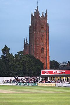 Cricket ground in front of church tower.