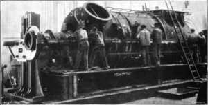 A large piece of machinery is in operation. Six workers can be seen attending to the machine while a ladder lies against it.