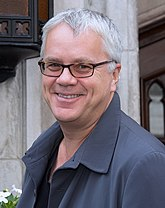 A standing caucasian man with short white and grey hair, wears glasses and a blue coat. He faces left towards the camera smiling.