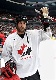 Todd Bertuzzi wearing a black helmet and white Canada jersey, waving to the crowd with his left hand