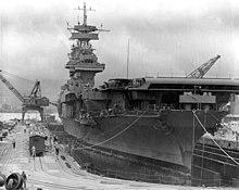 Porte-avions en cale vu de face légèrement en biais. Des ouvriers sont visibles au sol et sur le navire.