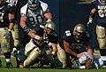 US Navy 041023-N-9693M-002 U.S. Naval Academy Quarterback Midshipman 1st Class Aaron Polanco is tackled after rushing for yardage in the first quarter of play against the Rice Owls.jpg