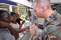 US Navy 070905-N-8704K-069 U.S. Air Force Capt. Brian Sydnor, attached to Military Sealift Command hospital ship USNS Comfort (T-AH 20), explains a child's prescription to her mother with help from Creole translator Ernst.jpg