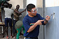 US Navy 090205-N-1688B-056 Gunner's Mate 3rd Class Santos Oyoque, assigned to the amphibious transport dock ship USS Nashville (LPD 13), scrapes cracked paint before re-painting the walls of the Centoe Mecico Social clinic.jpg