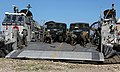 US Navy 100122-M-8605C-004 Marines unload vehicles and supplies from a landing craft air cushioned onto a Haitian beach.jpg