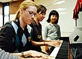 US Navy 100220-N-6855K-111 viation Ordnanceman 2nd Class Shannon Lanza nd Yeoman 2nd Class Christy Casavilla play Heart and Soul on the piano for Japanese children during a community relations project.jpg