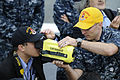 US Navy 110517-N-ER662-274 Damage Controlman 1st Class Branden Hadley gives a demonstration of equipment used during fires to Japanese media aboard.jpg