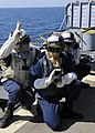 US Navy 110715-N-KB052-563 Boatswain's Mate 3rd Class John King, leader of hose team three, communicates with the on-scene leader during a crash a.jpg