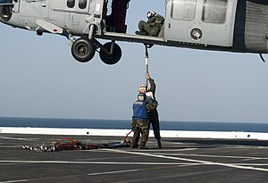 US Navy 120129-N-PB383-708 Airman Sarah McGee holds Master Sgt. Joseph Kelly as he attaches cargo to an MH-60S Sea Hawk helicopter embarked aboard.jpg