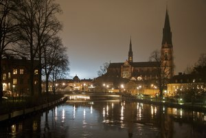 Uppsala Cathedral in background of the Fyris river at night.