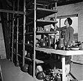 Vermoedelijk Eva Staer-Nielsen bij een stelling met keramieken vazen en schalen, Bestanddeelnr 252-8897.jpg