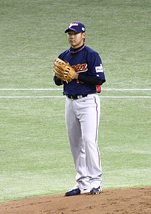 A young Japanese man wearing a dark blue and grey Japan national baseball uniform stands on a pitching mound.
