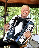 "Seated, smiling man with wire-frame glasses, playing a piano accordion that is decorated with the name ""OSTANEK""."
