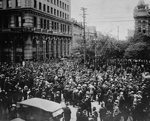 Large group of people in the middle of a city street beside a large concrete building