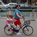 Woman pushing a bike with two kids.jpg