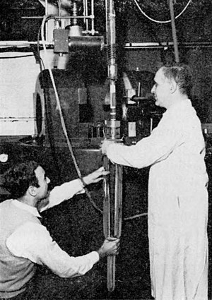 Wu experiment - The Wu experiment performed at the Bureau of Standards low temperature laboratory, Washington DC, in 1956.  The vertical vacuum chamber, containing the cobalt-60, detectors, and field coil, is being placed into a Dewar before being inserted into the large electromagnet in the background, which will cool the radioisotope near absolute zero by adiabatic demagnetization.