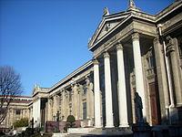 La façade d'un bâtiment en maçonnerie, avec quatre grecs ornant son entrée, sous un ciel bleu clair