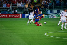 A man in a blue-and-red shirt is lying on the floor with his legs above his head. Behind him, a man in a white shirt is chasing after a football.