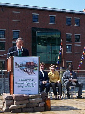 Byron Brown - Brown sits next to Sen. Hillary Clinton and Rep. Brian Higgins while Sen. Charles Schumer speaks at Erie Canal Harbor opening ceremony on July 2, 2008.