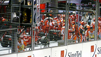 2008 Singapore Grand Prix - Ferrari mechanics work on Felipe Massa's car during the safety car period while teammate Kimi Räikkönen waits behind him. The Brazilian was released with the fuel hose still attached to his car and nearly collided with Adrian Sutil.