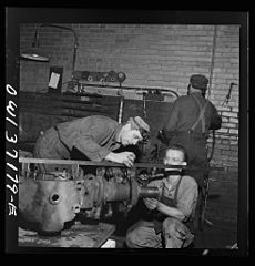 A mechanic working on a rear axle housing at the Greyhound garage 8d32907v.jpg