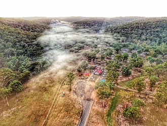 Yengo National Park - Aerial perspective of the Grey Gum International Cafe, nestled between the Yengo and Wollemi national parks on an autumn morning. February 2018.