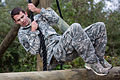 An Army Junior Officer Training Corps cadet uses a rope to swing over a log while navigating an obstacle course located on the 7th Special Forces Group (Airborne) compound.jpg