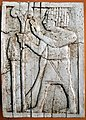 An Egyptian-looking man holds a lotus flower on a long stalk. Nimrud ivory. Sulaymaniyah Museum.jpg