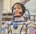 Anne McClain in front of the Soyuz spacecraft mockup.jpg