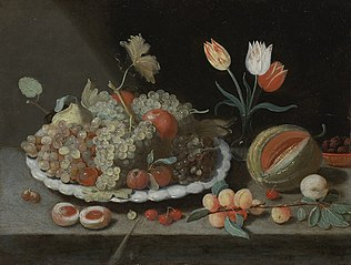 Still life with grapes and other fruit on a platter, a glass vase with tulips, a melon, apricots, cherries and other fruits, all on a ledge