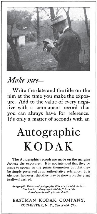 Timestamp - Advertisement for a 1915 Kodak Autographic camera. The picture shows a photographer writing directly onto the film inside the camera. He may have been recording the date of the photograph that he had just taken.
